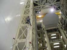 Worker safely makes his way down a highbay structure