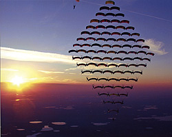81 skydivers fly in formation at sunset.