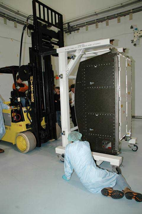 A technician works unloading the new environmental control and life support system.
