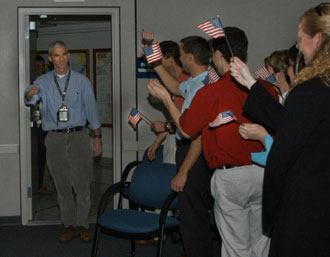 NASA engineer Bill McQuade is welcomed back to Kennedy Space Center by fellow workers.