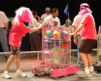 Members of the Pink Team prepare their robot