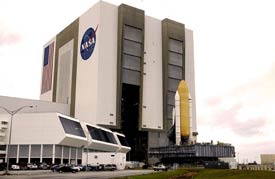 The Vehicle Assembly Building alongside a rolling space shuttle.