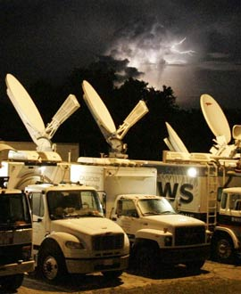 Lightning streaks across the sky above satellite trucks at Kennedy Space Center's Shuttle Landing Facility.