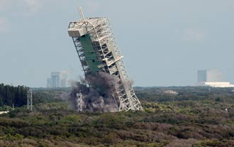Strategically placed explosives topple the launch gantry at Launch Complex 36.