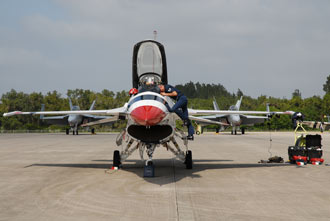 A crewman readies a Thunderbird jet for its performance.