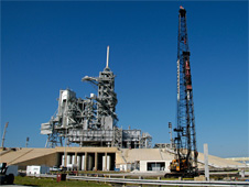 A crane lifts a piling that will be pounded into the ground at Launch Pad 39B.