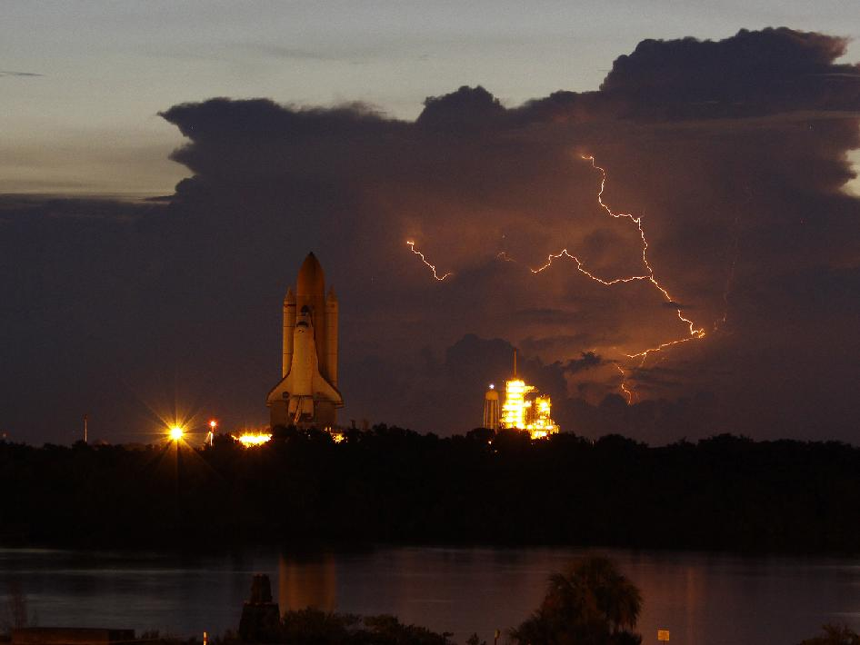 Space shuttle Discovery heads to the launch pad with lightning in the background.