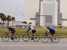 Cyclists ride past the Vehicle Assembly Building.