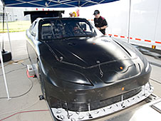 Mechanics and driver prep a NASCAR race car for testing.