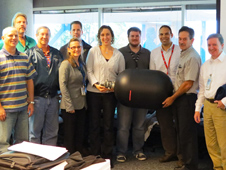 The Kennedy Space Center team holds an engineering model of the Nitrogen Oxygen Recharge System Recharge Tank Assembly at a system design review held at the Johnson Space Center.