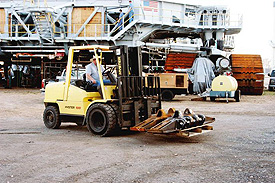 A KSC worker uses a forklift to offload the newly arrived crawler shoes to a staging area.