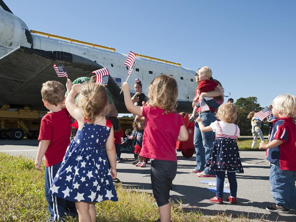 Children waving flags greet space shuttle Atlantis.