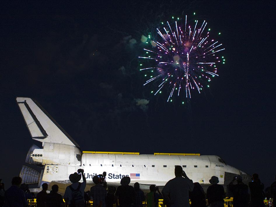 Space shuttle Atlantis in the foreground with fireworks in the sky.