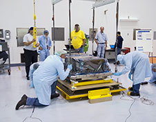 Workers inside the Space Station Processing Facility at Kennedy Space Center position the orbital replacement unit.