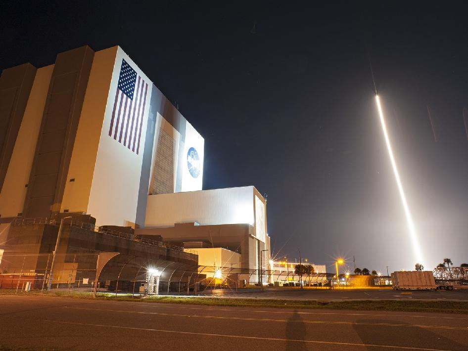 With the VAB in the foreground, the Atlas V rocket climbs overhead.