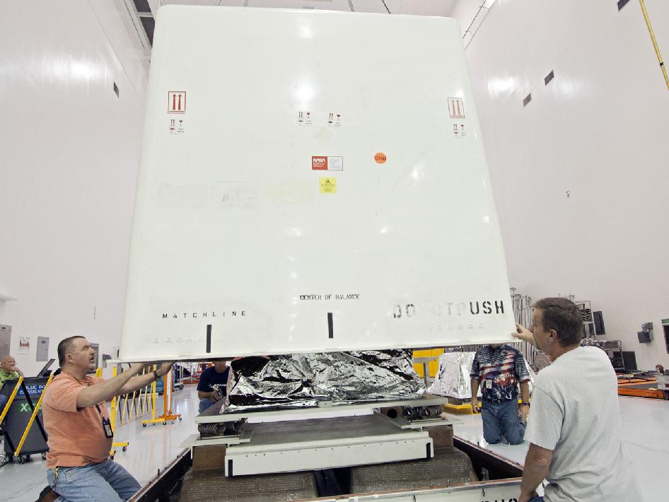 Workers prepare the payload container for shipment.
