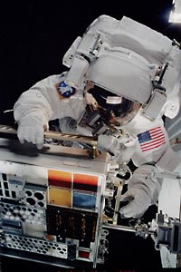 Close-up of astronaut working with a MISSE container