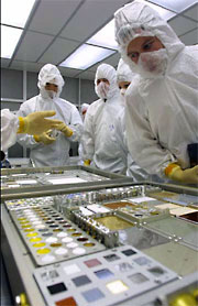 Researchers examine the materials of a MISSE Passive Experiment Container (PEC) in a clean room at NASA Langley