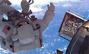 Astronaut approaches an open MISSE Passive Experiment Container attached to the International Space Station