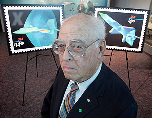 some dude stands in front of two blown-up copies of the x-planes stamps at their unveiling ceremony on mar. 17 in the virginia air and space center. photo by jeff caplan.