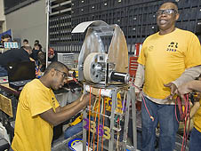 NASA Langley U.S. Army employee Chester Langston (R) works with Menchville High School senior Demetrius Adams