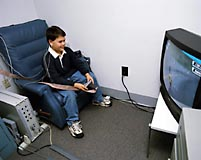 Child (Justin) is shown playing an instrumental video game.