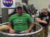 Brandon Hogan (L) and Devon Cooley (R) test NASA's High School students United to Create Hardware (HUNCH) chair that will be used to teach pilots and astronauts how abrupt head movements affect aircrew members during flight.