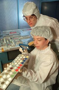 Researchers examine colorful coatings destined for the International Space Station as part of the MISSE experiment
