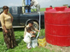 A family in the northern Iraq village of Kendala samples fresh water from a new well-water purification system that has its origins in the space program.
