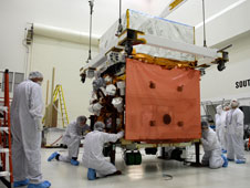 In the Astrotech payload processing facility, General Dynamics technicians watch as GLAST is moved toward a work stand (left) to check GLAST's scientific instruments.