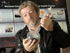 "Dr. Ed Ethridge holds his ""moon in a bottle"" experiment in his lab at the Marshall Center."