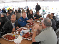 STS-133 Mission Specialist Timothy Kopra talks with MAF employees while enjoying some Louisiana crawfish. Kopra and the STS-133 crew visited MAF Mar. 22 to meet with employees and tour the plant.