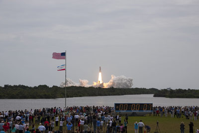 Members of the media and employees gather near the countdown clock to see this rocket's red glare for the last time as space shuttle Atlantis roars off Launch Pad 39A at the Kennedy Space Center.