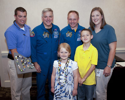 Seven-year-old Sydney Newton, front row left, is presented with Beads of Courage from STS-134 astronauts Gregory Johnson and Michael Fincke, back row center, during the July 13 crew visit to Marshall, while her family looks on.