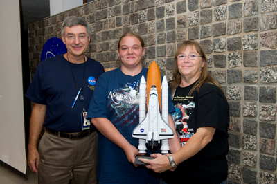 Marshall Exchange Operations Manager Edwin Jones, left, congratulates Marshall human resources specialist Deborah Allen, right, and her daughter Brandy Allen, center, for winning the 1:100 scale Atlantis full shuttle stack model autographed by the entire crew of STS-135 at the Marshall Exchange Shut