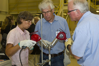 Using heat guns to open a U.S. sample cartridge processed in space are, from left, German researchers Dr. Petra Neuhause and Dr. Harold Lenski, and Jeff Clancy of Teledyne Brown Engineering.