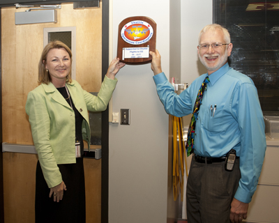 From left, Shuttle Operations Coordinators Lynn Farris and Kirk Teitge hang a commemorative plaque in the Payload Operations Center in Building 4663.