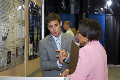 Marshall Space Flight Center summer intern Kurt Kienast, left, a mechanical engineering student at Rice University, explains friction stir welding to Gail Gordon, branch chief of Marshall's Materials and Processes Lab, during the Aug. 3 Summer Intern Poster Day event.