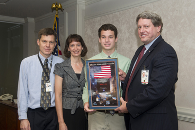 Matthew Volz, second from right, is awarded a 2011 NASA College Scholarship by Marshall Deputy Director Gene Goldman, right, while Volz's parents Martin and Sue, look on.