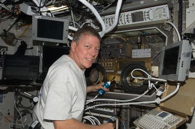 Expedition 28 Flight Engineer Michael Fossum works with Shear History Extensional Rheology Experiment, or SHERE, hardware inside the Microgravity Science Glovebox on the International Space Station in August.