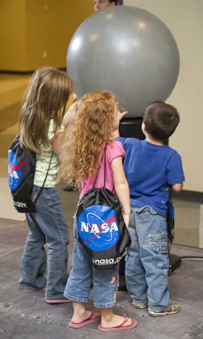 Children ponder a globe of the moon at the International Observe the Moon Night event at the Educator Resource Center in Huntsville.