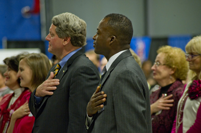 Siran Stacy, at right foreground, and Deputy Director Gene Goldman, left foreground, pay respects to the National Anthem at the Combined Federal Campaign rally.