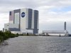 The Vehicle Assembly Building towers over two tugboats sitting alongside the Pegasus Barge moored in the Turn Basin at Kennedy Space Center, Fla. The barge departed Nov. 10, towed by NASA's Freedom Star ship to Stennis Space Center, Miss.