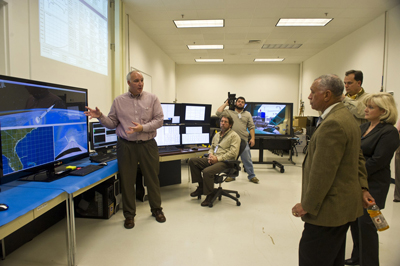Drew Hall, left, system integration lab lead for the Hardware-in-the-Loop Simulation Lab, explains how the Space Launch System's flight software, avionics and hardware are integrated to Charles Bolden, at right in the foreground, while local media and Jody Singer look on.