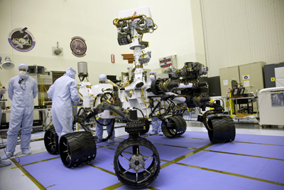 Technicians at the Jet Propulsion Laboratory look over Curiosity.