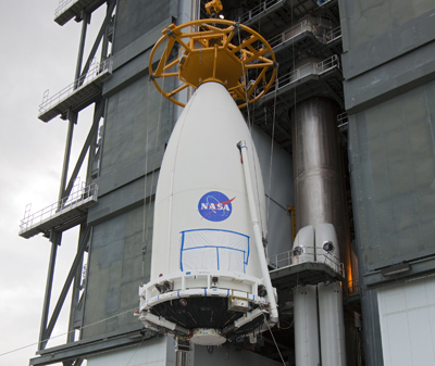 The Mars Science Laboratory, bolted inside the payload fairing of an Atlas V rocket, is hoisted into place on the launch pad.