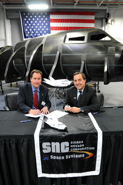 Robert Lightfoot, left, director of NASA's Marshall Space Flight Center, and Mark Sirangelo, head of Sierra Nevada Space Systems of Louisville, Colo., sign a Space Act Agreement.