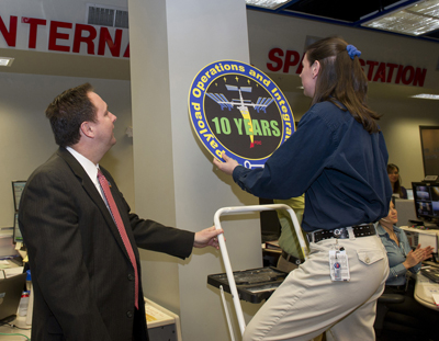 Marshall Center Director Robert Lightfoot, left, assists Jenn Whitworth, a Payload Rack Officer, in hanging a plaque in the Payload Operations Center. The plaque commemorates the team�s 10 years of continuous support to the International Space Station.