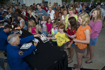 Astronaut Lee Morin hands an autographed picture to a child during the one of the two autograph sessions during the