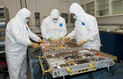 From left, Dr. Gary Pippin of Boeing Research & Technology; Brandon Krick, a student at the University of Florida; and Marshall Center engineer Miria Finckenor open the MISSE-7B suitcase to begin disassembly and analysis.